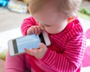 Child trying to chew a mobile phone